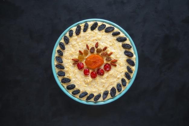 Owsianka owsiana z suszonymi owocami na czarnym stole. widok z góry.