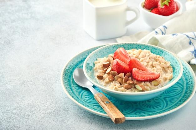 Owsianka owsianka z plastrami truskawek, orzechami, migdałami i miodem w niebieskiej misce na szarym stole. zdrowe odżywianie, diety, wegetariańskie jedzenie koncepcja. miejsce na tekst