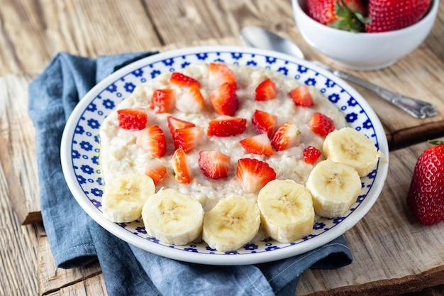 Owsianka owsianka z truskawkami i bananem na drewnianym stole w stylu rustykalnym. zdrowe śniadanie ze świeżymi organicznymi jagodami.