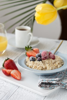 Owsianka śniadaniowa z jagodami owoców i filiżanką kawy. płatki owsiane z truskawkami i jagodami. zdrowe śniadanie pyszne domowe angielskie śniadanie koncepcja na tle.