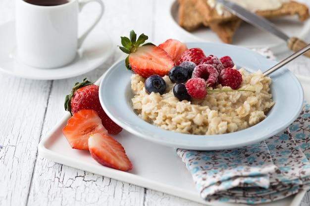 Owsianka śniadaniowa z jagodami owoców i filiżanką kawy.