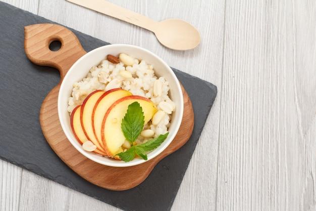 Owsianka sorgo z kawałkami brzoskwini, orzechów nerkowca i migdałów w porcelanowej misce z łyżką na drewnianych i kamiennych deskach. wegańska bezglutenowa sałatka z sorgo z owocami.