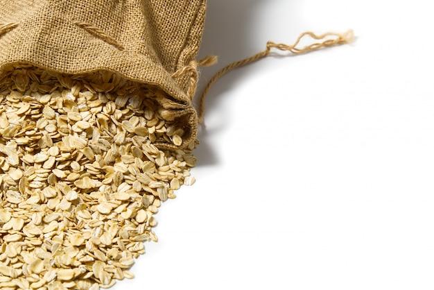 Owsianka wysypuje się z lnianej torby. suche naturalne płatki owsiane. naturalna lniana torba ekologiczna z płatkami owsianymi
