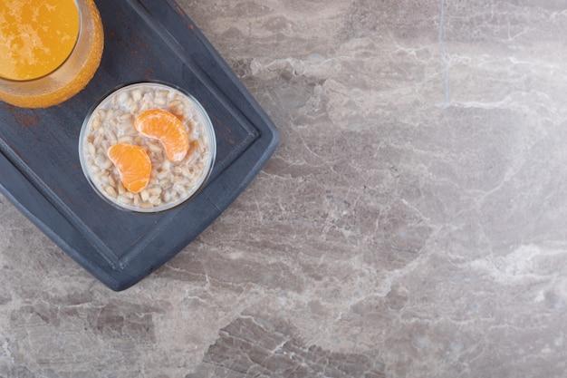 Owsianka z dwoma plastrami pomarańczy w szklance na drewnianej tacy obok soku pomarańczowego, na marmurowym tle.