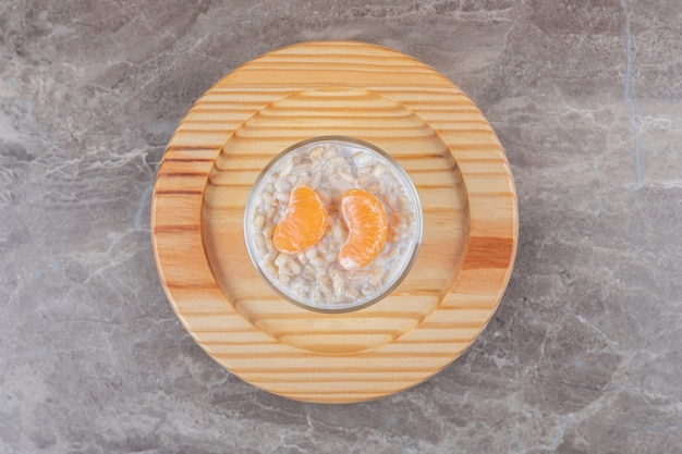 Owsianka z dwoma plastrami pomarańczy w szklance na drewnianym talerzu, na marmurowym tle.