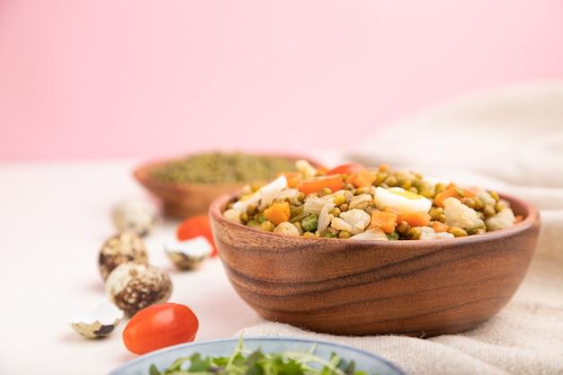 Owsianka z fasoli mung z jajkiem przepiórczym, pomidorami i drobnozielonymi kiełkami na biało-różowej powierzchni i lniana tkanina