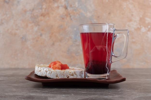 Owsianka z plastrami pomidora w szklance na drewnianym talerzu, na marmurowej powierzchni