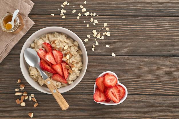 Owsianka z plastrami truskawek, orzechami, migdałami i miodem w misce na starym ciemnym drewnianym stole. zdrowe odżywianie, diety, wegetariańskie jedzenie koncepcja. miejsce na tekst