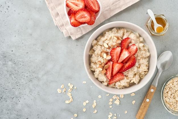 Owsianka z plastrami truskawek, orzechami, migdałami i miodem w misce na szarym stole. zdrowe odżywianie, diety, wegetariańskie jedzenie koncepcja. miejsce na tekst