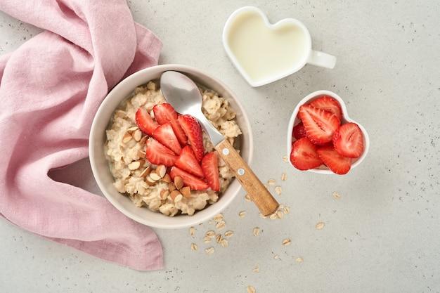 Owsianka z plastrami truskawek, orzechami, migdałami i miodem w niebieskiej misce na szarym stole. zdrowe odżywianie, diety, wegetariańskie jedzenie koncepcja. miejsce na tekst
