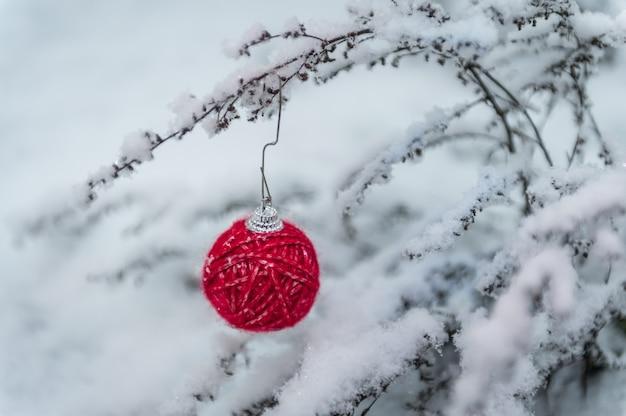 Ozdoba choinkowa wykonana z czerwonej przędzy na naturalnym śniegu