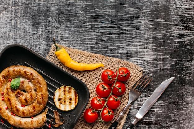 Ozdoba kiełbasa ślimaka z czerwonym pieprzem i liści bazylii na patelni na tle z teksturą