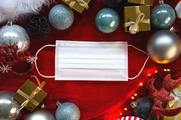 Ozdoba świąteczna i biała ochronna maska medyczna na twarz covid-19, leżąca na płasko