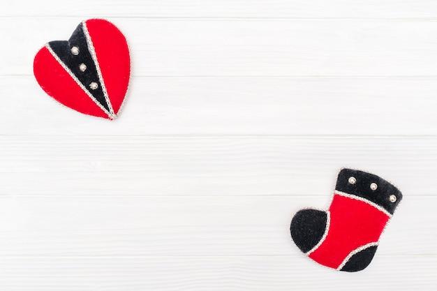 Ozdoba świąteczno-noworoczna wykonana z ramy narożnej z ozdobami noworocznymi serca i buta