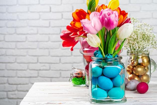 Ozdoba wielkanocna. bukiet kwiatów z kolorowymi jajkami
