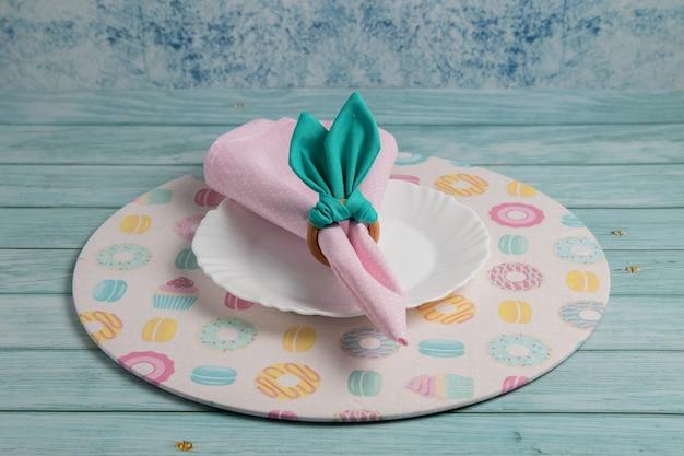Ozdoba wielkanocna z różową serwetką, obrączką na serwetki przypominającą uszy królika, białym talerzem i sousplatem tematycznym. niebieskie tło.