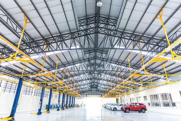 Ozdobą wnętrza jest posadzka epoksydowa budynku przemysłowego lub dużego centrum napraw samochodowych ze stalową konstrukcją dachu