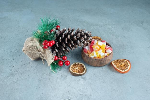 Ozdoba wykonana z szyszki sosnowej obok suszonych plasterków cytryny i miseczki z cukierkami na marmurze.