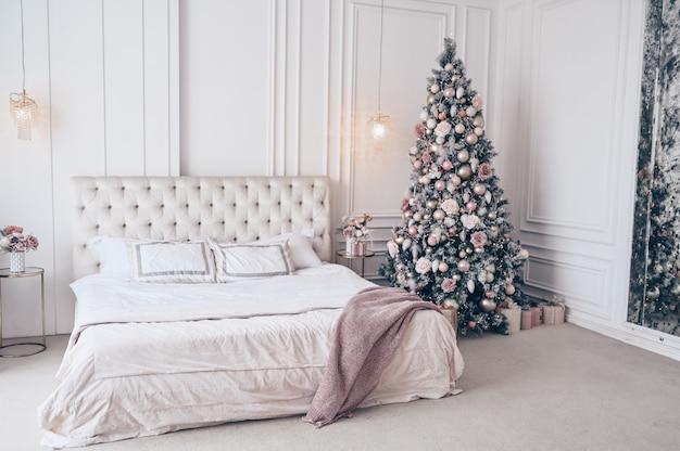 Ozdobiona choinka w białym klasycznym wnętrzu sypialni z świątecznym bukietem w wazonie
