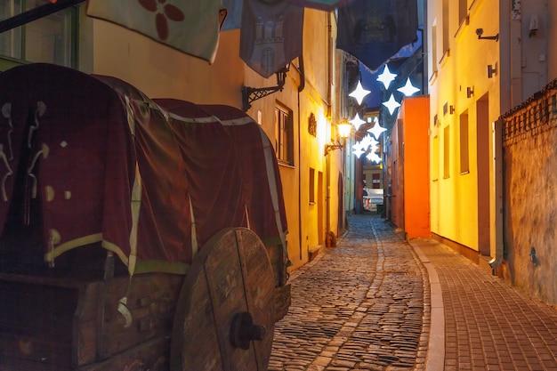 Ozdobiona i oświetlona świąteczna ulica starego miasta w nocy, ryga, łotwa