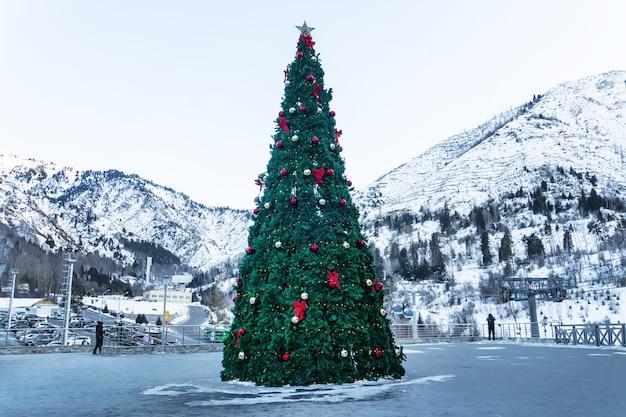 Ozdobiona pięknymi kulkami i girlandami sylwestrowe drzewo stojące na górach w tle.