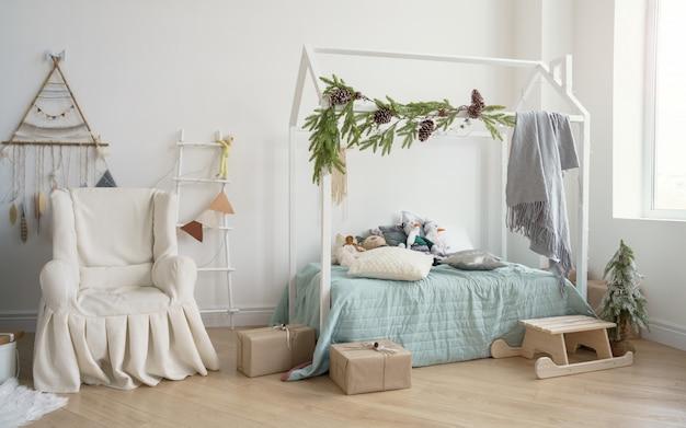 Ozdobiona sypialnia dziecięca z zadaszonym fotelem i łóżkiem w kształcie domu