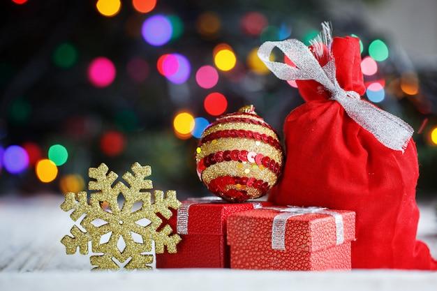 Ozdobione prezenty świąteczne i złoty płatek śniegu, worek świętego mikołaja na kolorowe światła.