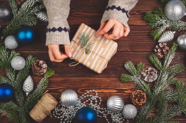 Ozdobiony prezent ze wstążką w otoczeniu ozdób choinkowych na drewnianym stole