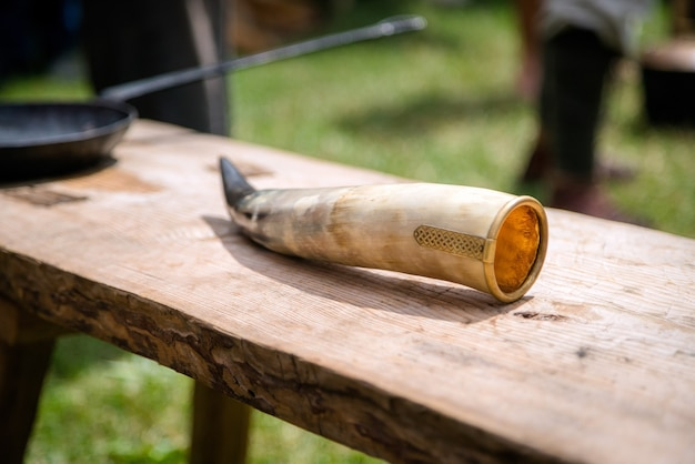 Ozdobiony róg zwierzęcy z metalowym grawerem na naczynie na wino leżące na drewnianym stole
