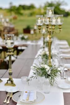 Ozdobiony stół na uroczystości weselne z siedzeniami dla gości na zewnątrz w ogrodach z płonącymi świecami