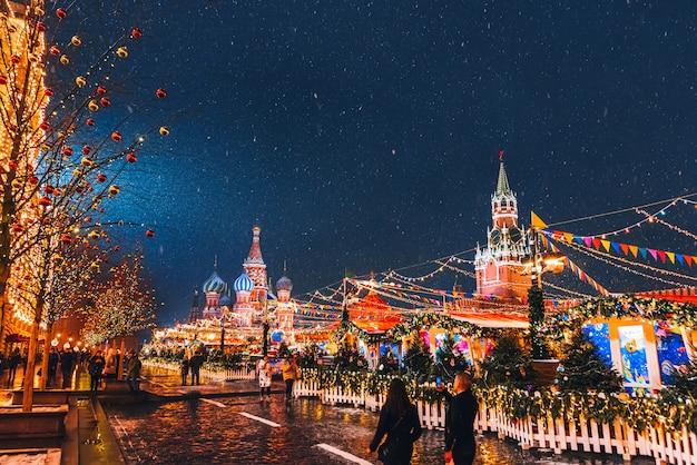 Ozdobiony świątecznym czerwonym placem w moskwie z katedrą św. bazylego i wieżą spasskaya nocą w zimie