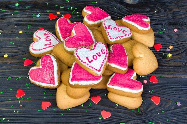 """Ozdobiony walentynki. stos ciasteczka z polewą, w kształcie serca z napisem """"miłość""""."""