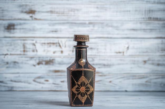 Ozdobna butelka ceramiczna w kolorach czarnym, czerwonym i złotym, malowana butelka na białym tle drewnianych, z bliska. ozdobna butelka porcelanowa malowana farbami akrylowymi, rękodzieło, malowanie punktowe
