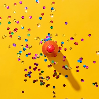 Ozdobna czerwona malowana butelka wina z twardymi cieniami i kolorowym konfetti na żółtym tle, miejsce. widok z góry. kartka świąteczna