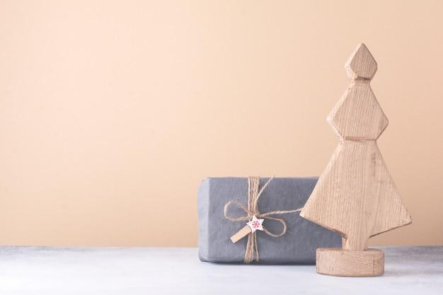 Ozdobna drewniana choinka i prezenty zawinięte w gwiazdę, stożek i tkaninę, na jasnym tle. koncepcja zero odpadów