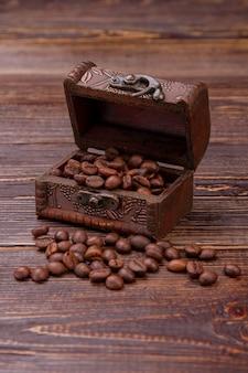 Ozdobna drewniana skrzynia wypełniona ziarnami kawy