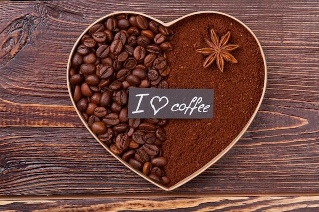 Ozdobna forma serca wykonana z ziaren kawy i kawy rozpuszczalnej. widok z góry z góry. powierzchnia drewniana .