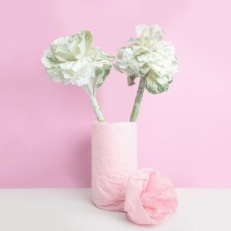 Ozdobna kapusta w wazonie, owinięta różowym papierem na różowej ścianie