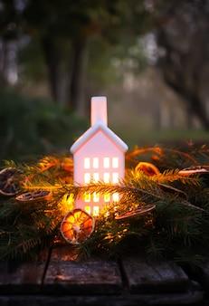 Ozdobna latarnia domowa z płonącą świecą w jesiennym parku wieczorem.