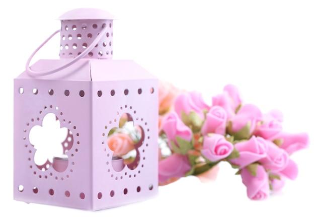 Ozdobna metaliczna latarnia i sztuczne kwiaty na białym tle