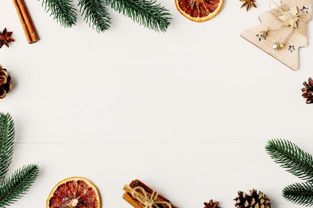 Ozdobna rama, atrybuty świąteczne na białym drewnianym stole. miejsce na tekst, puste na pocztówkę. copyspace.
