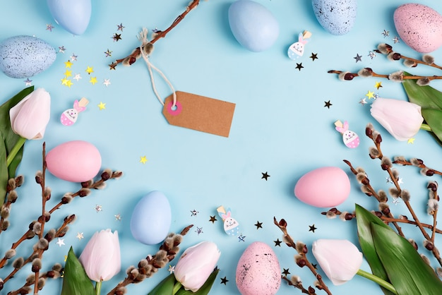 Ozdobna rama z rękodziełem wielkanocnym, malowane jajka, kwiaty tulipanów i papierowa etykieta na jasnoniebieskim tle.