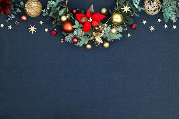 Ozdobna świąteczna granica, kwiecista girlanda z eukaliptusa, bombki, drobiazgi i czerwona poinsecja. czerwony, zielony, złoty świąteczny wystrój na klasycznym niebieskim lnie
