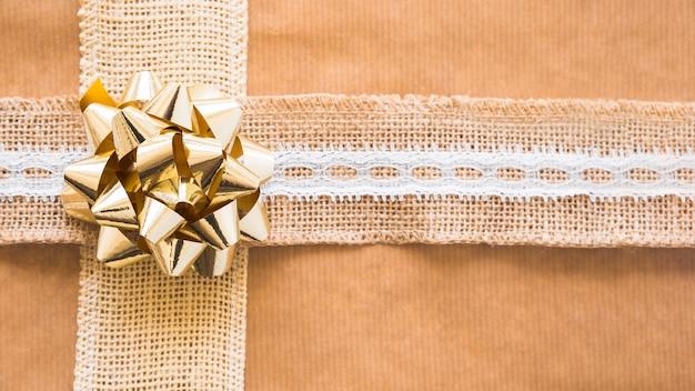 Ozdobna wstążka tkania i złoty łuk na papierze prezent