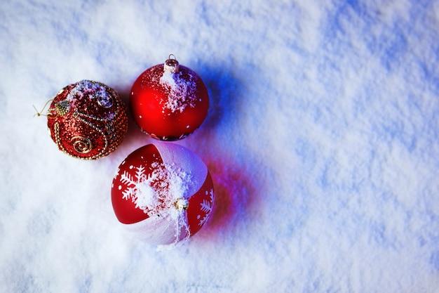 Ozdobne bombki w śniegu z niebieskim podświetleniem.