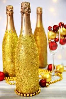Ozdobne butelki szampana z koralikami i bombkami na jasnym tle