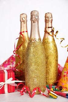 Ozdobne butelki szampana z serpentynami na jasnym tle