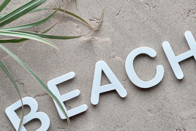 """Ozdobne drewniane litery """"plaża"""" na mokrym piasku z liśćmi palmowymi"""