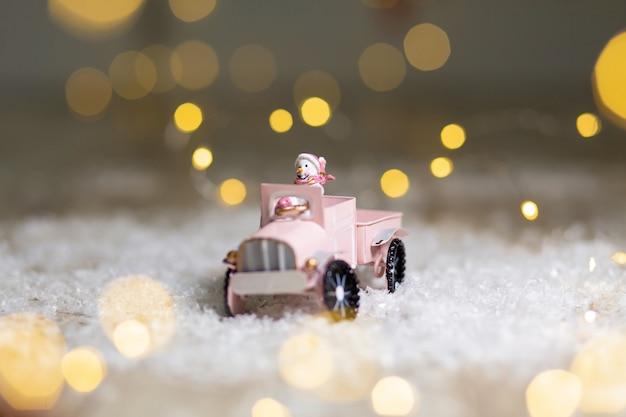 Ozdobne figurki o tematyce bożonarodzeniowej, statuetka świętego mikołaja jeździ na samochodziku z przyczepą na prezenty,