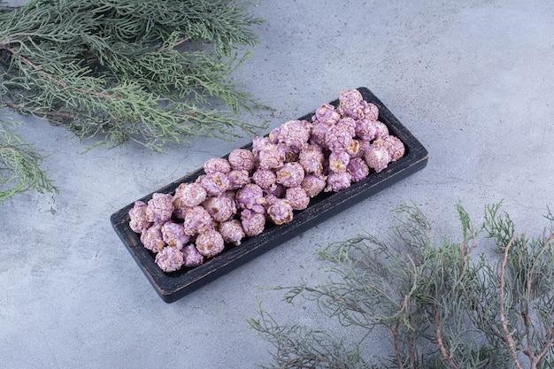 Ozdobne gałązki z tacką z popcornem pokrytym cukierkami pośrodku na marmurowej powierzchni